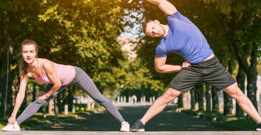 fit-fitness-woman-man-doing-stretching-exercises-outdoors-park